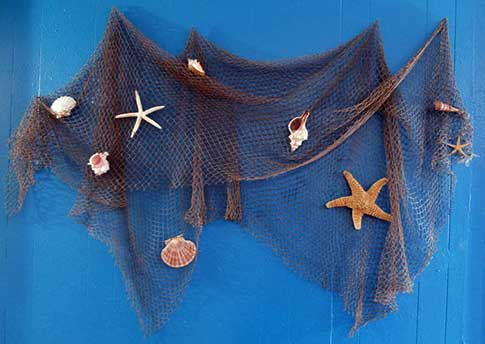 Fish net hung on blue wall decorated with seashells and starfish.